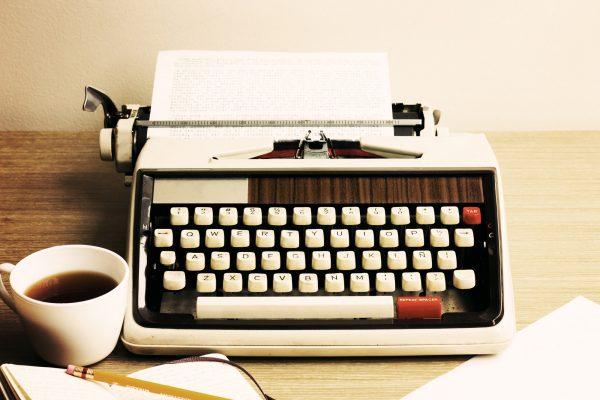 Vintage typewriter and coffee cup
